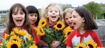 Group of Brownies laughing holding sunflowers